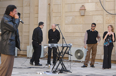 Hussein Al-Assadi, an Iraqi, performs a microphone check for the band Groove Alliance in the Green Zone.                                             (Gulf Region Division Public Affairs Office)