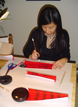"Wendy writes auspicious sayings (""Fai Chun"") on red paper using ink she made herself.                                             (Charlie Schroeder)"