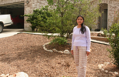 Arshia Khurshid stands in her front yard, where she has replaced a grass lawn with rocks, mulch and trees.                                             (Michael May)