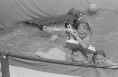Jane Bratton, waving in the photo, and her two siblings, in the backyard pool that they built with their mother.                                             (Jane Bratton)