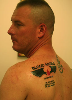 Medic Clint McCullough shows off his memorial tattoo with the name of his unit, and the names of three friends who died.                                             (Michael May)