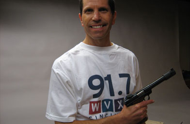 "Eric, in his public radio t-shirt, with his gun. He likes to listen to ""Fresh Air"" while shooting.                                             (Katie Orr)"