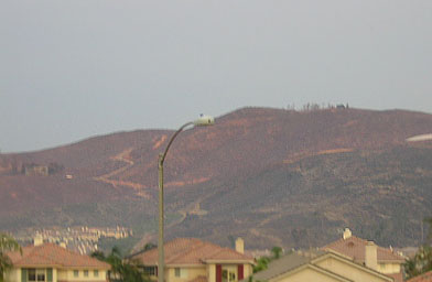 Larry Himmel, a television reporter, did a report in front of his burning house. His house was out on that hill somewhere. At the top of the hill you can see some trees. There used to be a large blue house where those trees are. At the far left you can also see a fuzzy silhouette of a destroyed home.                                             (John Vogel)