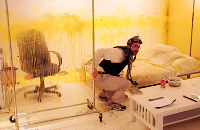 "Iraqi born artist Wafaa Bilal keeps low to prevent from getting shot by paintballs in his ""Domestic Tension"" exhibit at the Flatfile Galleries  Chicago.                                             (Scott Olson / Getty Images)"