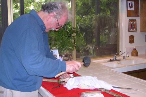 "Japanese sword expert Richard Suran, trys to pry off the sword handle, or ""Tsuka,"" to reveal the ""Tang"" (the bottom part of the blade inside the handle), where the sword maker usually puts his signature.                                             (Krissy Clark)"