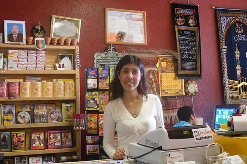 Mariya Sher Ali works behind the counter at her store, Amarillo International Food.  The store caters to Amarillo's growing refugee population and stocks foods from all over the world.  It also rents Bollywood movies.                                             (Ann Heppermann and Kara Oehler)
