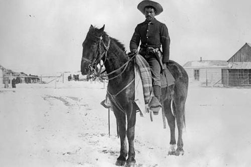 A Buffalo Soldier from Denver's 9th Cavalry on snow-covered ground in 1890.                                             (- - -)