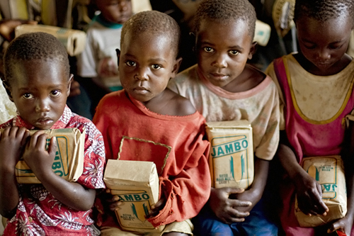 Orphans hold packs of flour distributed to them by a businessman in a Kenyan church. The young children's parents were victims of widespread violence that has swept the country since disputed elections sparked simmering tensions in the country on Dec. 27, 2007.                                             (Yasuyoshi Chiba/AFP/Getty Images)