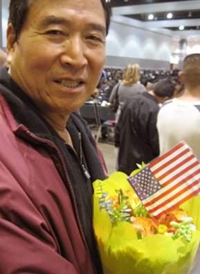 "Angela's father, Jong, waits for the ceremony to begin. On the day of the event, people entering the building are split up into ""new citizens"" and ""guests."" New citizens funnel inside and take their seats where they recite the loyalty oath and receive their naturalization papers.                                             (Angela Kim)"