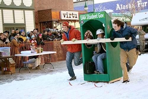 "University of Alaska Anchorage students (the back of their outhouse reads ""We're #1...and #2!) race down Anchorage's Fourth Avenue during the Fur Rendezvous Outhouse Races.                                             (Anchorage Convention &Visitors Bureau/Cady Lister)"