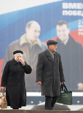"Pedestrians in central Moscow walk past an election poster depicting Russian President Vladimir Putin (left) and his chosen successor Dmitry Medvedev. A slogan on the poster reads: ""Together we will win!""                                             (Oleg Nikishin/Epsilon/Getty Images)"