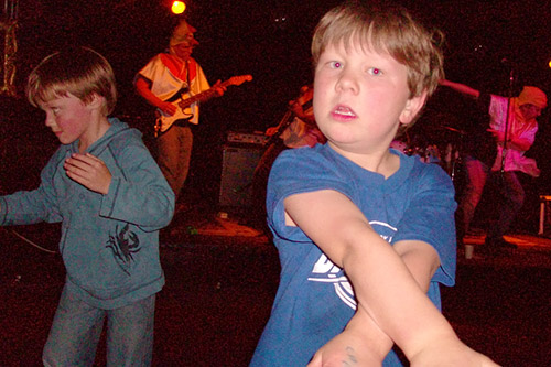 Charlie (foreground) and Ryan rock out on the dance floor while their fathers rock out on stage.                                             (Jill Moe)