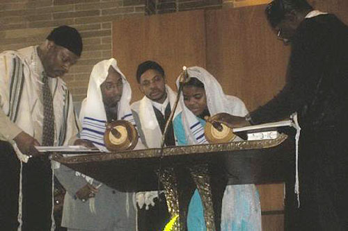 Tammy McCullough, studying to be a rabbi, reads from the Torah with temple leaders.                                             (Photo courtesy Temple Beth Shalom)