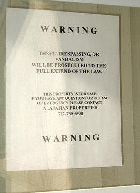 A sign on a foreclosed house meant to deter vandals.                                             (Krissy Clark)