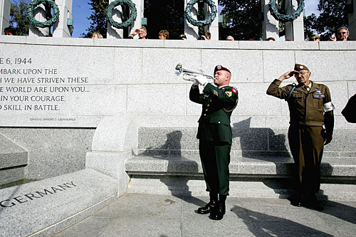 A trumpeter plays taps as Korean War veteran Edward Bottge salutes during a Veterans Day ceremony at the World War II memorial in Washington, D.C.                                             (Joe Raedle/Getty Images)