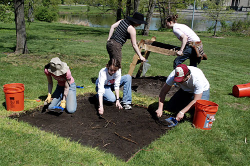 This shallow unit is one of the four squares being excavated in the park. Students Sarah Pickman, Caitlin Wylie and Dana Snitzky use trowels to dig through the topsoil, while Teacher's Assistant Mary Leighton and student Darian Gier sift through buckets of dirt for artifacts.                                             (Rebecca Graff)