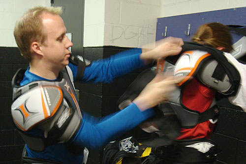 "Benjamin Salisbury helps his wife Kelly get suited up before their hockey class. ""The first day, it was like you were literally just a knight at Medieval Times,"" Benjamin Salisbury says. ""You're literally just weighed down.""                                             (Charlie Schroeder)"