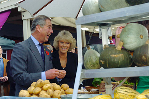 Prince Charles and wife Camilla, Duchess of Cornwall, share a laugh as they tour the West Marin Farmer's Market during a visit to Point Reyes in 2005. The prince is a prominent advocate of organic farming techniques.                                             (Frankie Frost-Pool/Getty Images)
