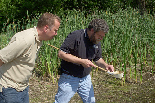 "John Moe and Mike McLean use a ""dipper"" to examine a pond that is a popular hangout for mosquitoes.                                             (Courtesy John Moe)"
