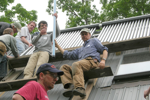 The volunteers form an assembly line to pass the light-weight solar tubes up the roof to where they're set into place.                                             (Shannon Mullen)