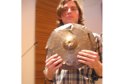 Broken Cymbal: Eric Hall shows off what some might consider to be a trashed cymbal.  To NOMO, it's part of their sound.                                             (Angela Kim)