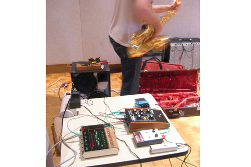Electronics Table: Elliot dashing from his collection of effects pedals to join his NOMO compatriots in the horn section.                                             (Angela Kim)