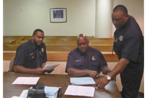 Officers Robert Mingus, Terrance Harris and Alvis Owen prepare for weekend arraignments.                                             (Desiree Cooper)