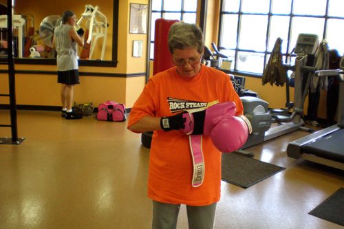 Mary Yeman, 60, puts on her pink boxing gloves at Rocky Steady Gym in Indianapolis, Ind.                                             (Colleen Iudice)