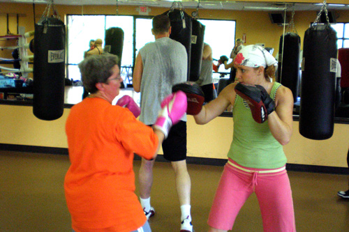 Mary Yeman and coach Kristy Follmar spar off during boxing class. During this drill, Yeman hits Follmar's hand pads.                                             (Colleen Iudice)