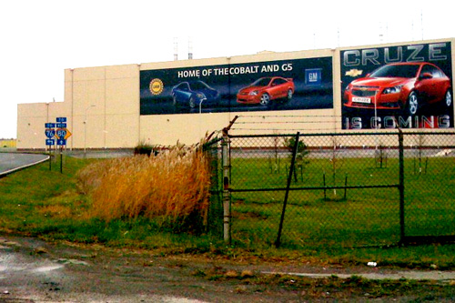 "This is the paint facility, only a portion of the massive Lordstown GM Assembly plant. The poster on the right says ""Cruze is coming."" The Chevy Cruze is a 5-passenger mid-size vehicle that will get 45 miles to the gallon and is seen as this plant, and this region's, potential lifesaver.                                             (Krissy Clark)"