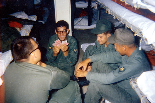 "Troops aboard the Walker play cards to pass the time. Although gambling was not permitted, some soldiers and Marines accumulated large sums of winnings from the pastime. As some troops remarked about disregarding the regulation, ""What were they going to do, send us to Vietnam?""                                             (Courtesy 1st Squadron, 1st Cavalry Regiment)"