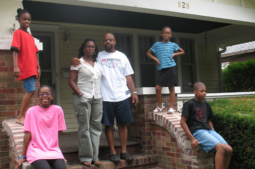 The Gilbert family in front of their old house in Bloomington, Ill.  Their new house is in the next town, Normal. The children, clockwise, from left:  Nia, age 9: Ayanna, age 7, Mark Jr., age 12, Imani, age 11.                                             (Laurie Stern)