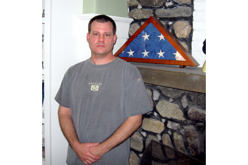 Scott L'Ecuyer, a former chief engineer for a nuclear missile silo, stands next to the American flag that flew on his base. The flag is a reminder of a crew mate who succumbed to the pressure and took his own life.                                             (Eric Molinsky)