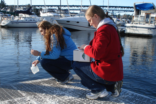 Volunteer scientists Liana Singh and Brittany Kimball demonstrate how to gather a water sample.                                             (Joshua McNichols)