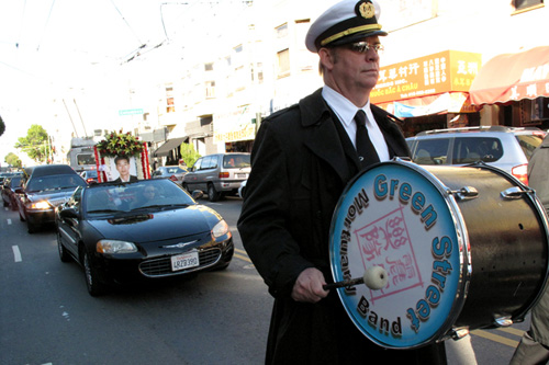 Tim Vaughn plays bass drum for the Green Street Mortuary Band. The picture car and hearse follow the band, leading the mourners through the streets.                                             (Julie Caine)