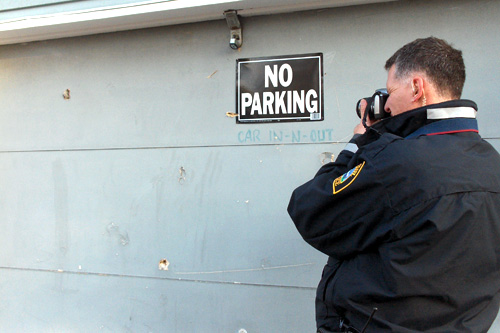 Officer Lundquist gets close up shots of stray bullets lodged in this garage.                                             (Marc Sanchez)