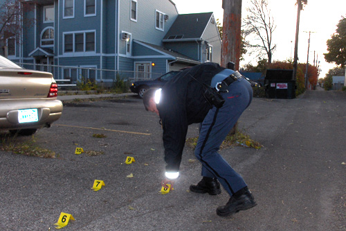 Officer Lundquist flags spent shell casings from a crime scene.                                             (Marc Sanchez)