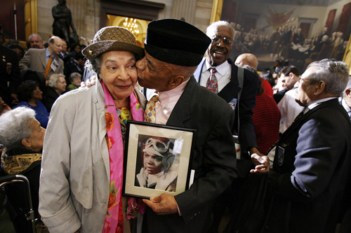Holding a photograph of himself as a 19-year-old pilot, Tuskegee Airmen Lt. Col. John Mulzac of Brooklyn, N.Y, kisses his wife Beatrice Mulzac after a ceremony honoring the World War II in Washington, DC.                                             (Chip Somodevilla/Getty Images)