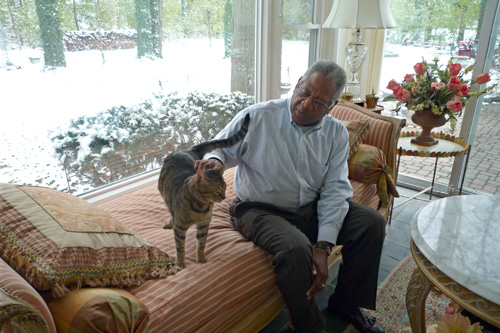 Romey enjoys a quiet moment with the family cat, Mr. Stripes. He feels he now has a peace of mind, no matter what the economy has in store.                                             (Desiree Cooper)